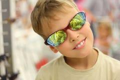 Weinig jongen die zonnebril in opslag probeert Stock Fotografie