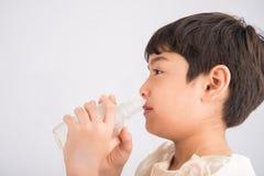 Weinig jongen die zout water gebruiken om zijn neus schoon te maken stock fotografie