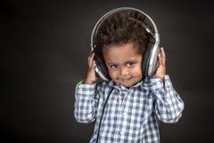 Weinig jongen draagt grote hoofdtelefoons stock fotografie