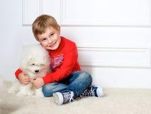 Weinig jongen drie jaar het oude spelen met witte puppy Stock Foto