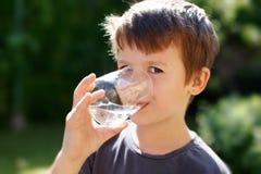 Weinig jongen drinkt water in aard Stock Fotografie