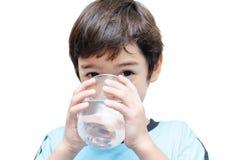 Weinig jongen drinkt water van een glas royalty-vrije stock afbeelding