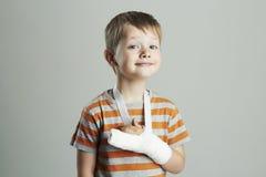 Weinig jongen in een castchild met een gebroken wapen grappig jong geitje na ongeval stock fotografie
