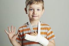 Weinig jongen in een castchild met een gebroken wapen jong geitje na ongeval Stock Fotografie