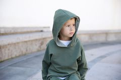 Weinig jongen in een hoodie op een bal in een park stock foto's