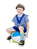Weinig jongen in een mariene kostuumzitting op de bal royalty-vrije stock afbeeldingen