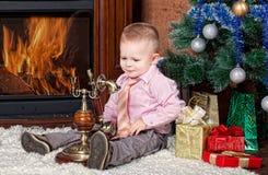Weinig jongen in een ruimte met een open haard Stock Fotografie