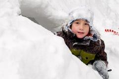 Weinig jongen in een sneeuwfort Stock Afbeeldingen