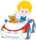 Weinig jongen in een stuk speelgoed auto Stock Afbeelding