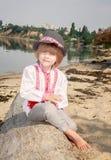 Weinig jongen in een witte geborduurde overhemd en een hoed zit op de rivierbank op een logboek stock afbeeldingen