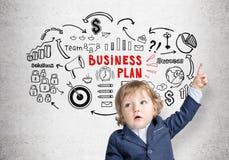 Weinig jongen en een schets van het businessplan op beton Royalty-vrije Stock Fotografie