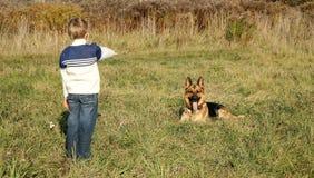 Weinig jongen en grote hond (Duitse herder) Stock Afbeeldingen