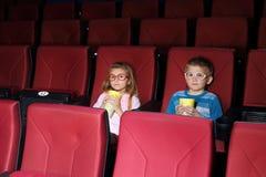 Weinig jongen en meisje die met popcorn op een film letten Stock Foto's