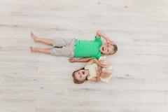 Weinig jongen en meisje die op de vloer liggen Stock Foto