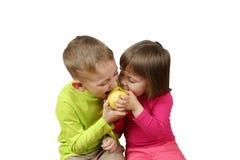 Weinig jongen en meisje eten gelijktijdig één appel stock afbeelding