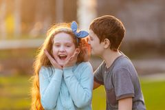 Weinig jongen en meisje fluisteren in openlucht in de lente stock foto's