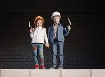 Weinig jongen en meisje in helmen bouwen huis Stock Afbeeldingen