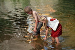 Weinig jongen en meisje in het water Stock Afbeeldingen