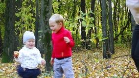 Weinig jongen en meisje, moeder hebben pret in de herfst stock videobeelden