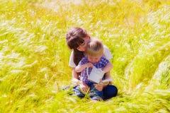 Weinig jongen en meisje op het de zomergebied met bloemen Royalty-vrije Stock Afbeeldingen