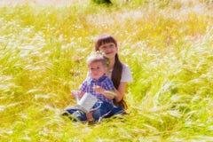 Weinig jongen en meisje op het de zomergebied met bloemen Stock Foto