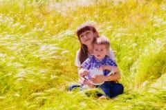 Weinig jongen en meisje op het de zomergebied met bloemen Stock Fotografie