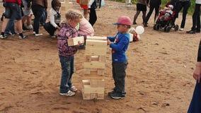 Weinig jongen en meisje spelen groot jengaspel op zand De zomerfestival Mensen, jonge geitjes stock footage
