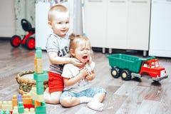 Weinig jongen en meisje spelen verstoord speelgoedmeisje royalty-vrije stock afbeeldingen