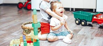 Weinig jongen en meisje spelen verstoord speelgoedmeisje stock foto