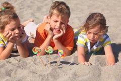 Weinig jongen en meisjes die op strand liggen royalty-vrije stock afbeeldingen