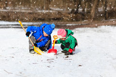 Weinig jongen en meisjes gravende sneeuw in de winter Royalty-vrije Stock Fotografie