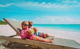 Weinig jongen en meisjes het drinken kokosnoot op strandvakantie stock afbeelding