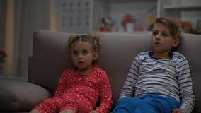 Weinig jongen en meisjes het letten op verschrikkingsfilm bij nacht, die op bank, vrije tijd zitten stock video