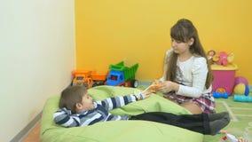 Weinig jongen en meisjes het spelen met stuk speelgoed tonometer in de ruimte stock video