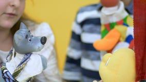 Weinig jongen en meisjes het spelen met zacht stuk speelgoed in het poppenspel in close-up stock video