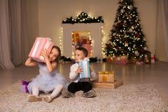 Weinig jongen en meisjes open Kerstmis stelt de nieuwe Kerstboom van de jaarwinter voor stock afbeeldingen