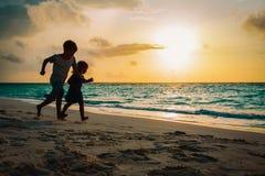 Weinig jongen en meisjeslooppas speelt bij zonsondergangstrand royalty-vrije stock afbeeldingen