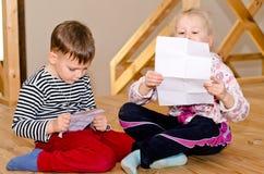 Weinig jongen en meisjeszitting die samen lezen Stock Foto's
