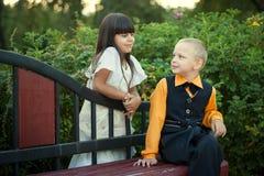 Weinig jongen en meisjeszitting op bank Royalty-vrije Stock Afbeeldingen