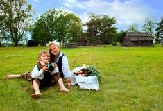 Weinig jongen en meisjeszitting op een gazon Royalty-vrije Stock Foto