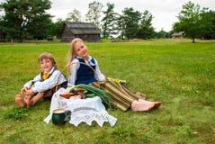 Weinig jongen en meisjeszitting op een gazon Stock Afbeelding
