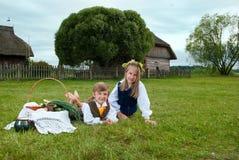 Weinig jongen en meisjeszitting op een gazon Stock Foto