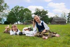 Weinig jongen en meisjeszitting op een gazon Royalty-vrije Stock Afbeeldingen