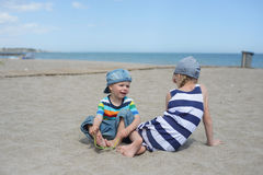 Weinig jongen en meisjeszitting op het strand Royalty-vrije Stock Afbeelding