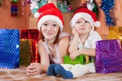 Weinig jongen en moeder in de hoed van de Kerstman Stock Foto