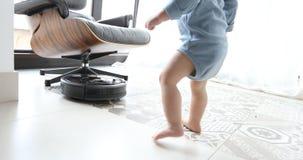 Weinig jongen en robot stofzuiger op de vloer stock footage