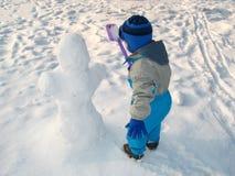Weinig jongen en sneeuwman Stock Fotografie