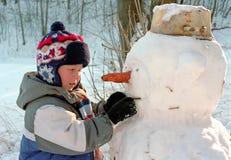Weinig jongen en sneeuwman Stock Foto's