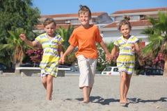 Weinig jongen en twee meisjes die op strand lopen royalty-vrije stock fotografie