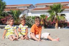 Weinig jongen en twee meisjes die op strand zitten royalty-vrije stock afbeelding